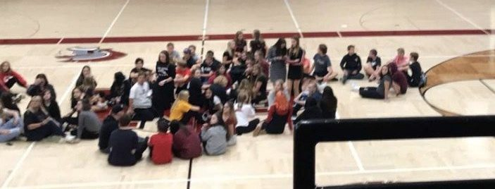 Students sit in the middle of the gym floor in protest of having the lights on during the Homecoming dance.