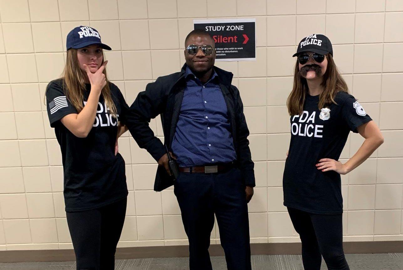 Georgia Trygestad and Cece Thoreson pose with Mr. Kordah as the PDA Police for Halloween.
