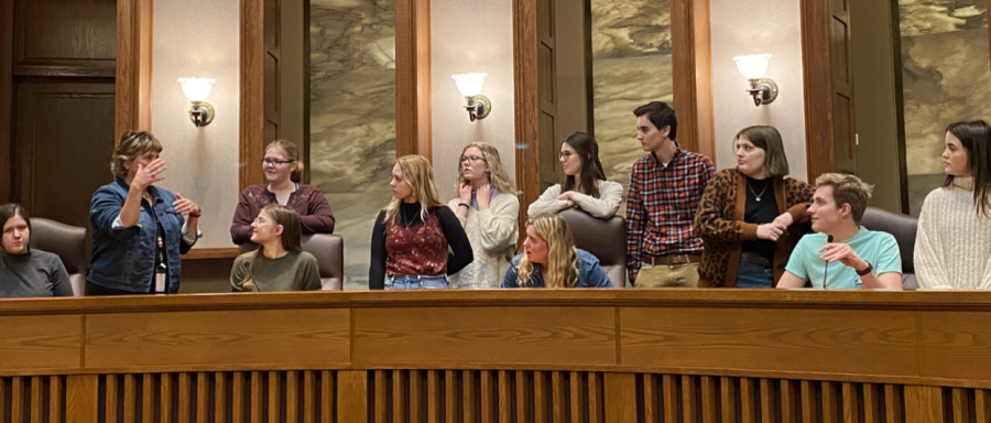 Justice McKeig explains to the class what it is like to be a judge on the Minnesota Supreme Court, along with showing students the hidden buttons and functions behind the stand. (Pictured from left to right) Ava Phillippi, Justice Anne McKeig, (in front) Sydney Mancini, (behind) Lydia Schmitz, Grace Knutson, Hannah Orr, (in front) Ella Ettlin, (behind) Ava Hart, Sullivan Hart, Sophia Bruder, Adam Langfield, and Elyse Thoreson. (Not pictured) Grace Madson, Aaron Paul, Juliet Garcia, and Carson Sayler.